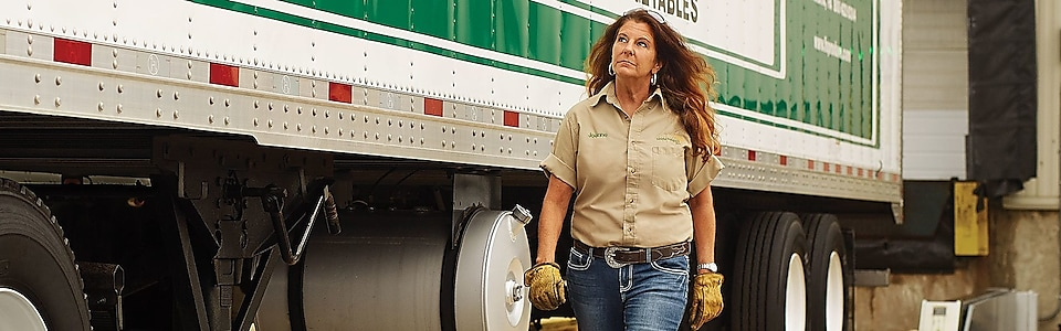 Female trucker walking beside tractor trailer